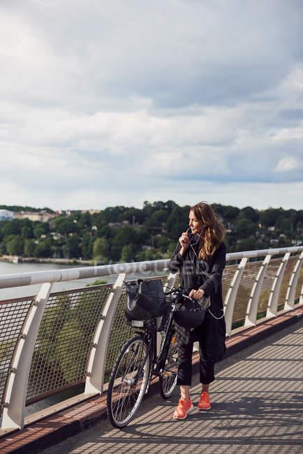 Femme mûre parlant à travers les écouteurs tout en marchant à vélo sur la passerelle contre le ciel — Photo de stock