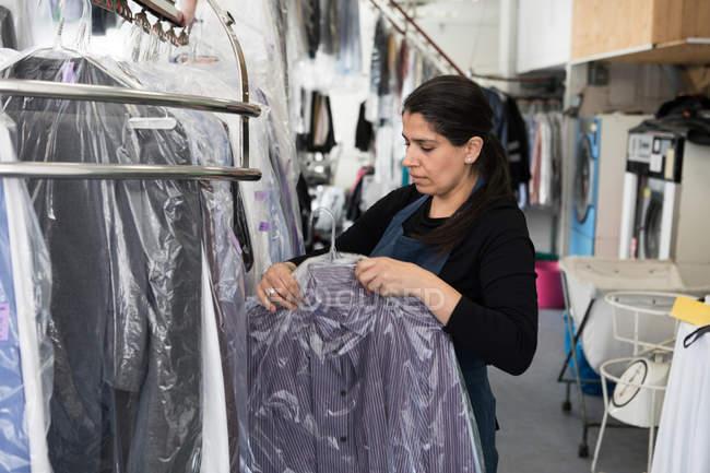 Доросла самотня суха прибиральниця, що тримає в пластику чисту сорочку, стоячи в Ландромат. — стокове фото