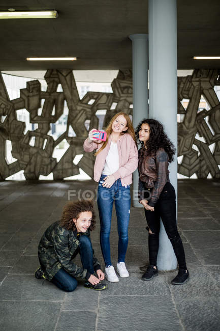Teenage girl kneeling by friends taking selfie at parking garage — Stock Photo