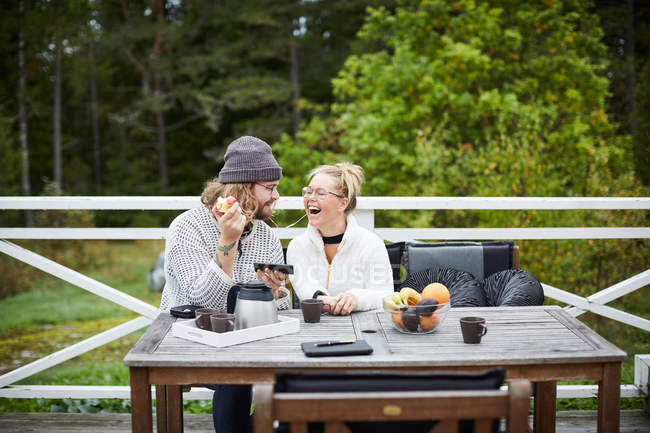 Male caretaker and disabled woman listening to music on smart phone at table in yard — Stock Photo