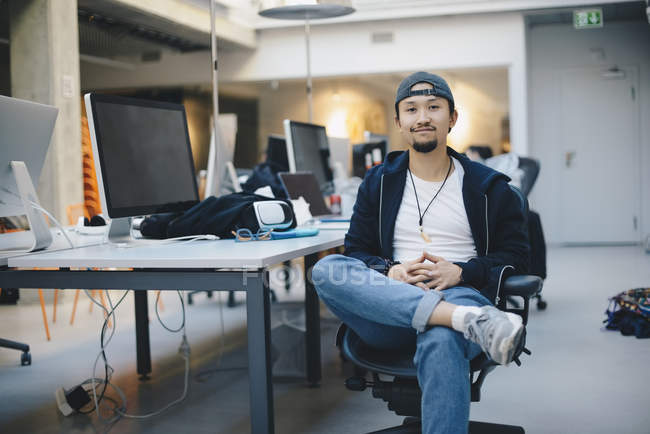 Portrait of confident male computer programmer sitting on chair in office — Stock Photo