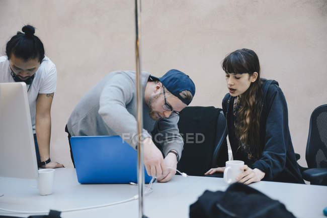 Computer programmer connecting cable laptop while colleagues at desk in office — Stock Photo