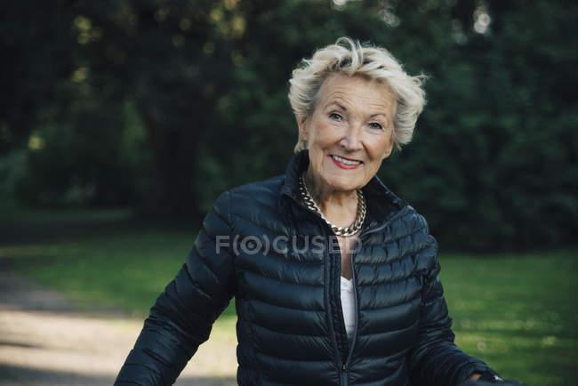 Portrait of happy senior woman wearing jacket in park — Stock Photo