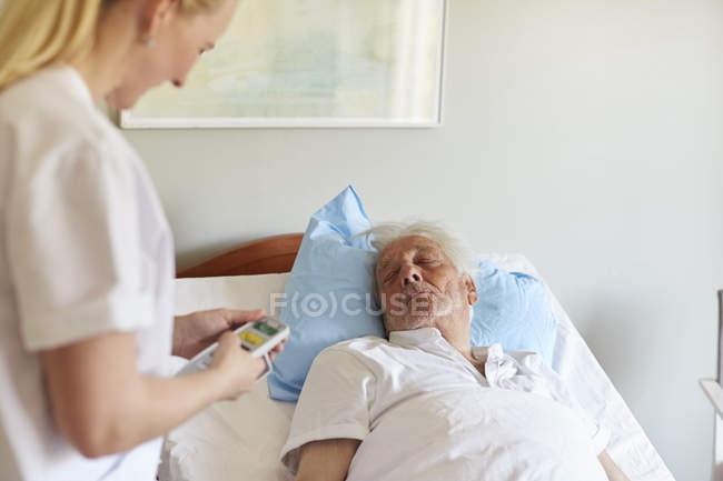 Side view of female nurse adjusting — Stock Photo