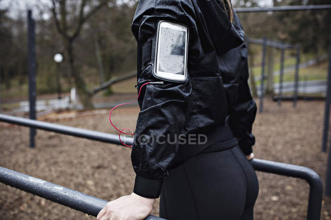 Rear view midsection of female athlete wearing arm band while exercising on parallel bars in forest — Stock Photo