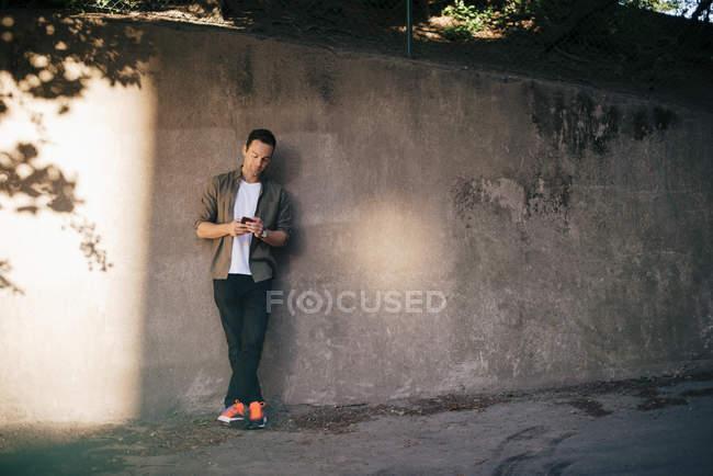 Uomo in piedi contro il muro durante l'utilizzo di smartphone — Foto stock