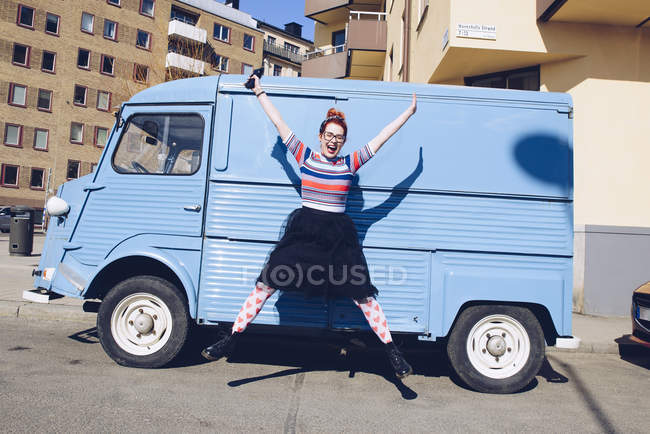 Full length of young woman jumping against blue mini van on city street — Stock Photo