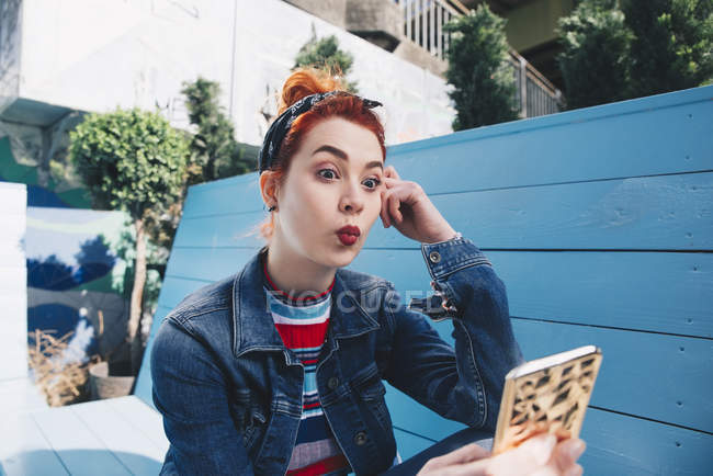 Redhead young woman taking selfie with mobile phone while sitting on bench — Stock Photo