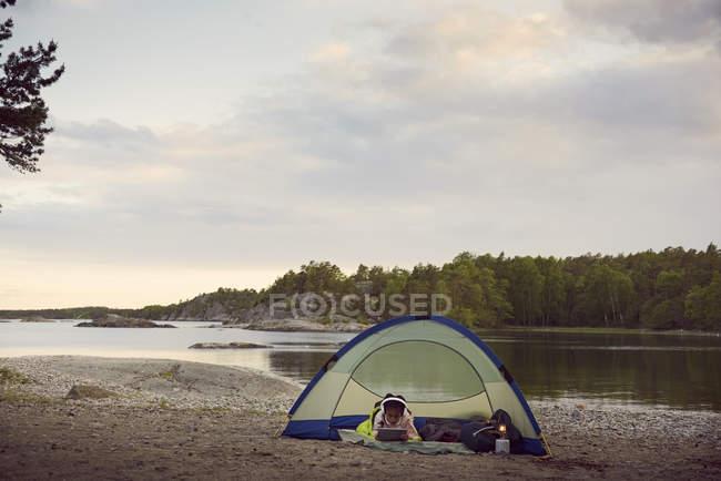 Menina usando tablet digital enquanto estava deitado na barraca na praia contra o céu durante o pôr do sol — Fotografia de Stock