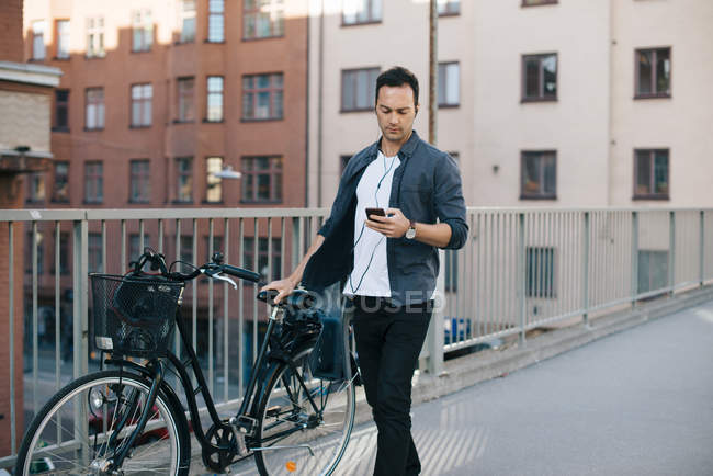 Man using mobile phone while walking with bicycle on footbridge against buildings in city — Foto stock