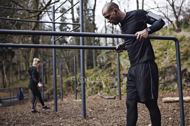 Atleti maschili e femminili in piedi alle barre parallele in foresta — Foto stock