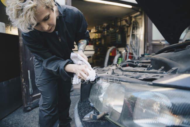 Female mechanic cleaning car headlight outside auto repair shop — Stock Photo