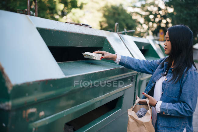 Teenage girl throwing packet in garbage can — Stock Photo