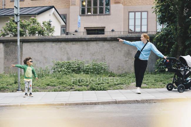 Menino apontando e mostrando a mãe com carrinho de bebê enquanto estava na calçada na cidade — Fotografia de Stock