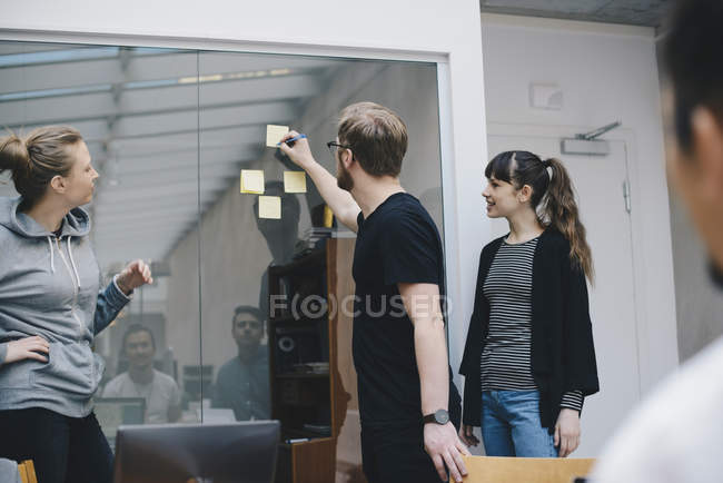 Computer programmer writing on adhesive note stuck on glass during meeting with colleagues in office — Stock Photo