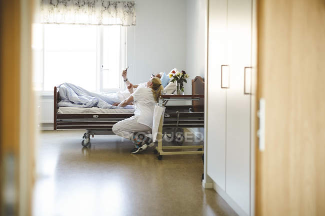Female nurse and senior man taking selfie with smart phone in hospital ward — Stock Photo