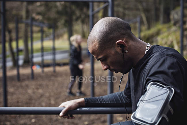 Side view of male athlete wearing earphones while exercising on parallel bars in forest — Stock Photo