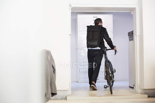 Rear view of businessman with bicycle walking in creative office — Stockfoto