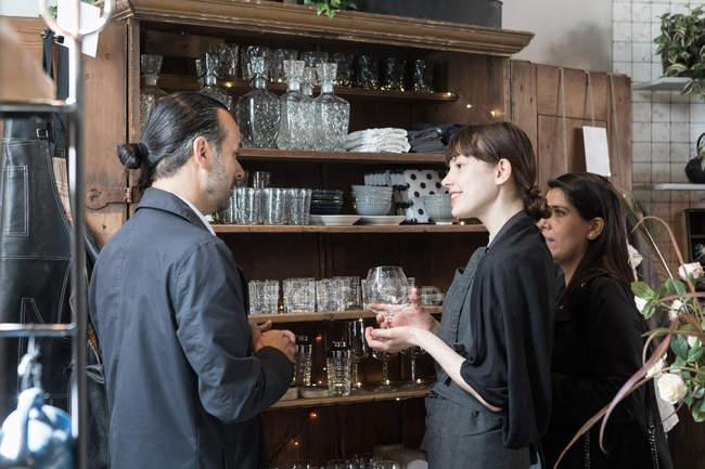 Jeune propriétaire femelle tenant du verre à vin tout en se tenant au milieu de clients matures au magasin — Photo de stock