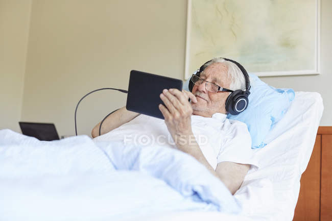 Senior man wearing headphones while using digital tablet on bed in hospital ward — Stock Photo