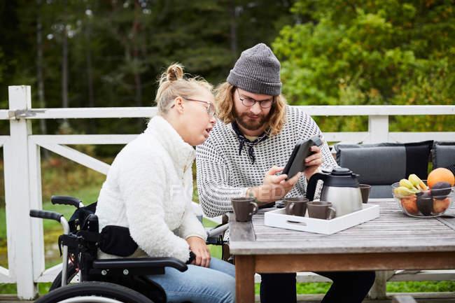 Young male caretaker using digital tablet with disabled woman in yard — Stock Photo