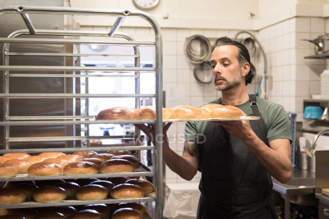 Confident mature male owner holding baking sheet with freshly baked breads on rack at bakery kitchen — Stock Photo