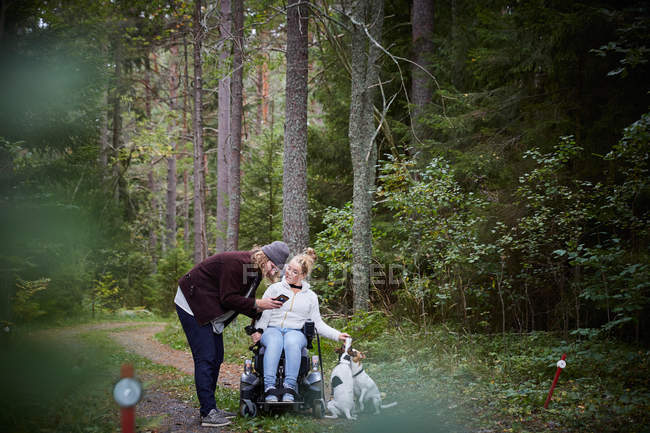 Male caretaker with disabled woman using mobile phone in forest — стоковое фото