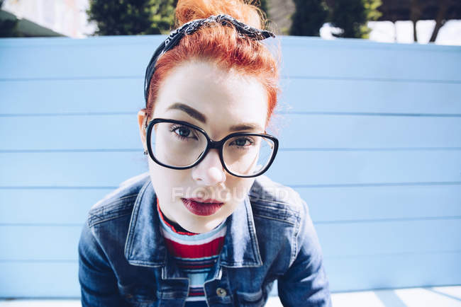 Portrait of redhead young woman wearing eyeglasses while sitting on bench — Stock Photo