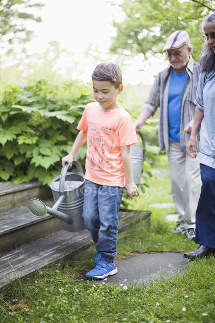 Boy carrying watering can with grandparents walking in back yard — Photo de stock