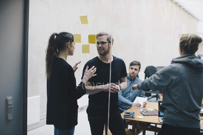 Programmeurs/programmeuses discutant au bureau vu à travers le verre — Photo de stock