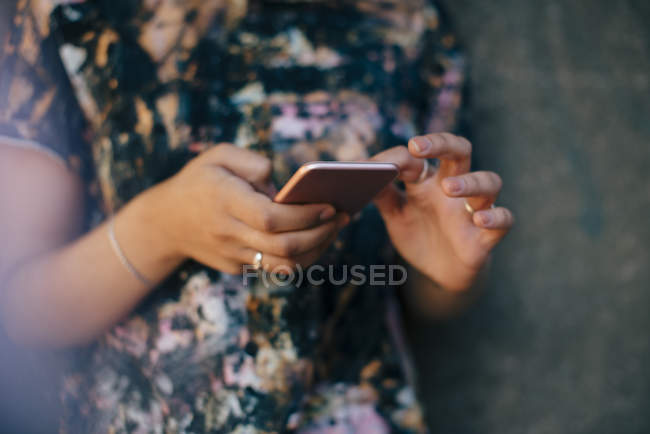 Midsection view of young woman using smart phone — Stock Photo