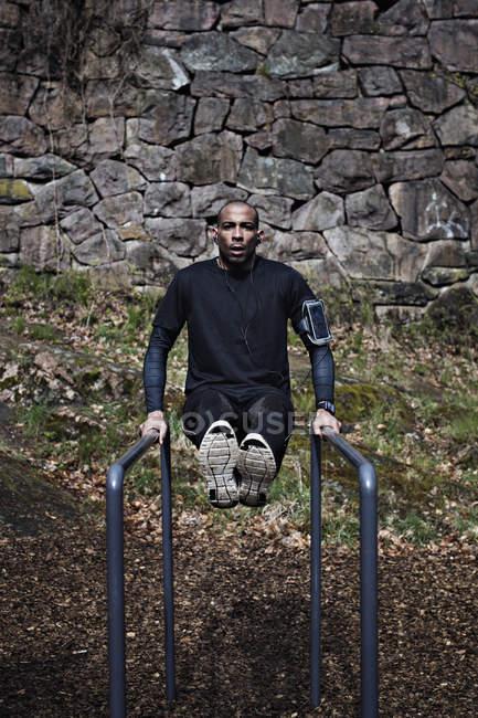 Athlète masculin exerçant sur barres parallèles dans la forêt — Photo de stock