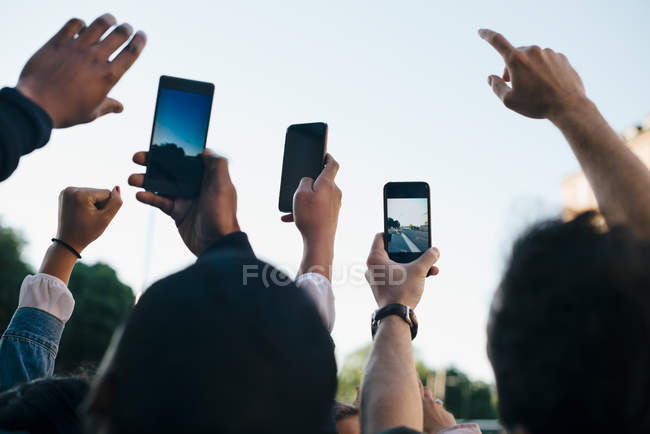 Low angle view of friends photographing from smart phones against sky — Stock Photo