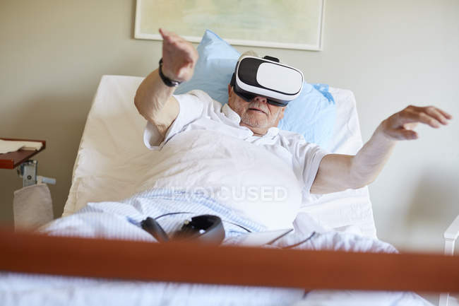 Surface level of senior man with arms raised using VR glasses on bed in hospital ward — Stock Photo