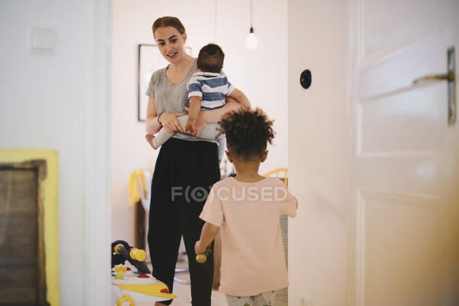 Madre portando bambino guardando il figlio mentre in piedi in camera domestica — Foto stock