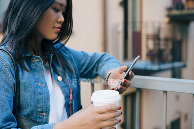 Teenage girl using smart phone while holding disposable coffee cup by railing — Foto stock