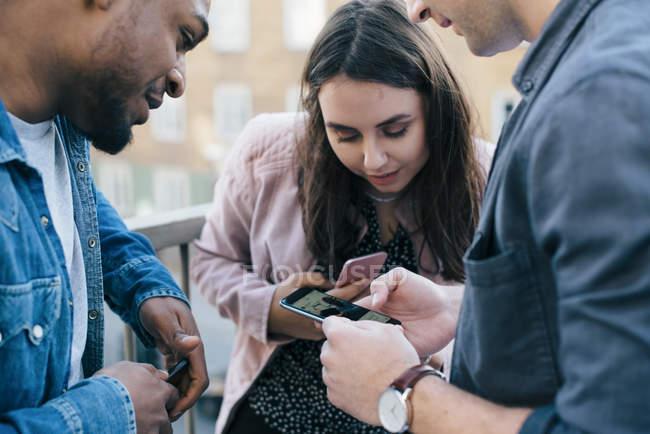 Amigos olhando para o homem usando telefone inteligente na cidade — Fotografia de Stock