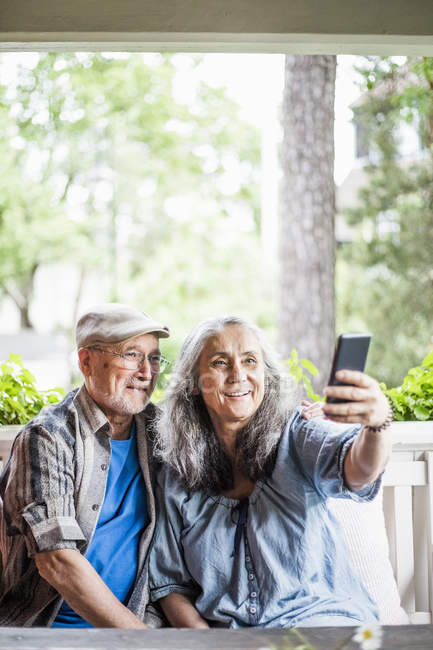 Smiling senior couple taking selfie in porch - foto de stock