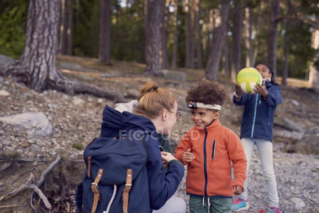 Mutter Blick auf lächelnde junge tragen Stirnlampe während Tochter spielen mit Fußball im Hintergrund — Stockfoto