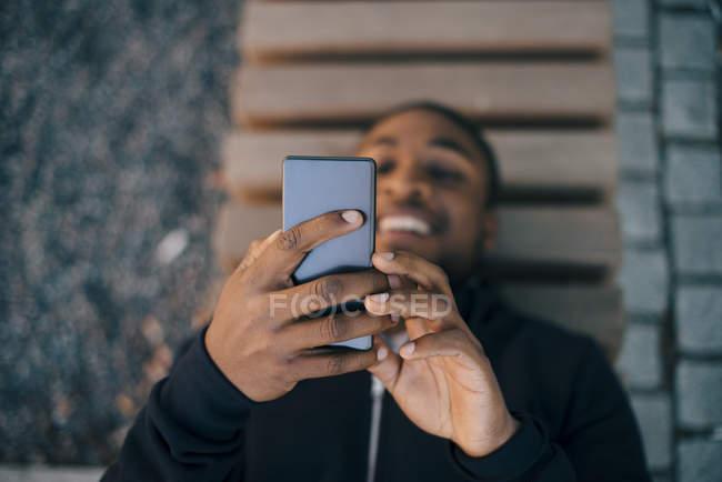 Vista ad alto angolo dell'uomo sorridente che utilizza lo smart phone mentre giace sulla panchina — Foto stock