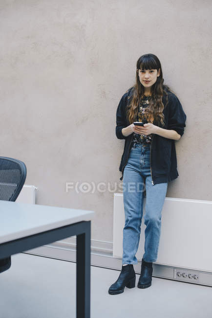 Full length portrait of female computer programmer holding smart phone while standing against beige wall in office — Stock Photo