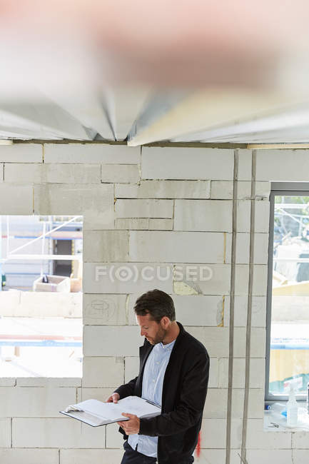 Mature architect reading document at incomplete building — Stock Photo