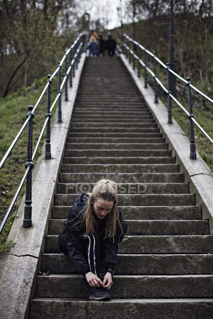 Повна довжина молоду жінку, пов'язуючи шнурок кроки — стокове фото