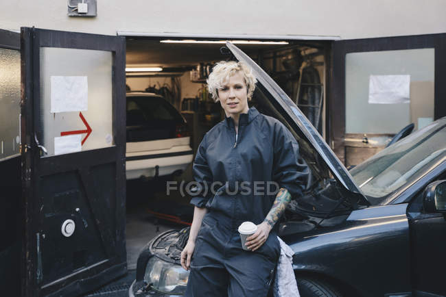 Portrait of confident female mechanic leaning on car outside repair shop — Stock Photo