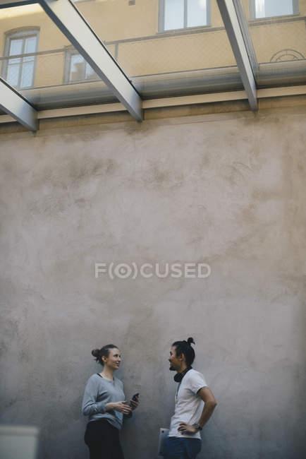 Programmeurs/programmeuses discutant contre le mur dans le bureau — Photo de stock