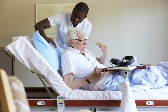Enfermeira masculina ajustando travesseiro para homem idoso na cama na enfermaria do hospital — Fotografia de Stock