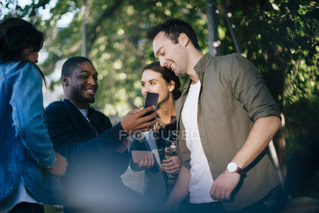 Low angle view of happy friends with mobile phones — Stock Photo