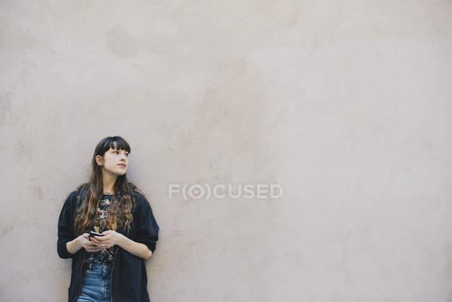 Programmatore di computer femminile premuroso che tiene lo smartphone mentre è in piedi contro la parete beige — Foto stock