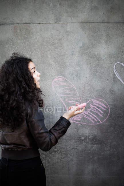 Vista posterior de adolescente dibujo en forma de corazón en la pared con tiza rosa - foto de stock