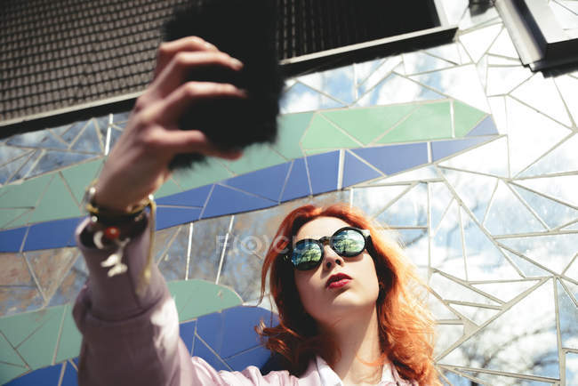 Low angle view of redhead young woman taking selfie with mobile phone against mosaic wall — Stock Photo